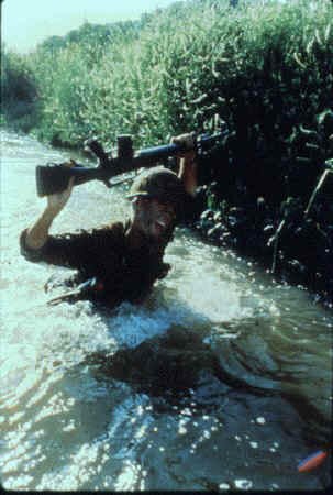 stephen caffrey holding M16 above head in water